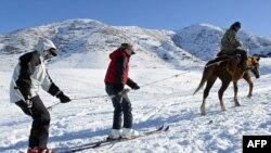 Қырғызстанда тауға шаңғымен серуендеуге бара жатқан шетелдік туристер (Көрнекі сурет).