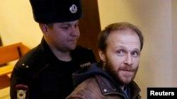Greenpeace белсендісі фотограф Денис Синяковты (оң жақта) сот залынан шығарып жатыр. Санкт-Петербург, 18 қараша 2013 жыл.