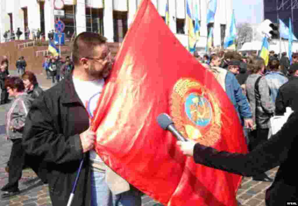 Nod To The Past - A coalition supporter holds a communist-era flag during the day's rallies. (photo: RFE/RL)