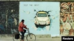 Un biciclist trece pe lângă o pictură stradală a unui Trabant. Mașina a devenit un simbol al căderii Zidului Berlinului după ce mai mulți germani au trecut granița dintre vest și est în 1989 într-un Trabant.