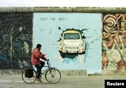 """Одно из самых известных изображений в East Side Gallery: """"Трабант"""", пробивающий Берлинскую стену"""