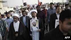 فردی که تصویری به دست دارد: شیخ علی سلمان، دبیرکل جمعیت الوفاق بحرین