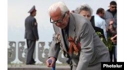 Armenia -- An elderly veteran lays flowers at a World War Two memorial in Yerevan, 9 May 2010.