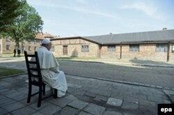 Погруженный в размышления Франциск перед бараками лагеря смерти Освенцим