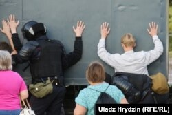 Riot police detain people on Prytytski Street in Minsk, near where Alyaksandr Taraykouski was killed during protests on August 10. Taraykouski was one of the first people to die in the postelection crackdown, which has claimed several lives.