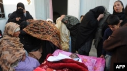 Shi'a mourn beside the body of a blast victim following the overnight suicide bomb attack on a Shi'ite procession in Rawalpindi on November 21-22.