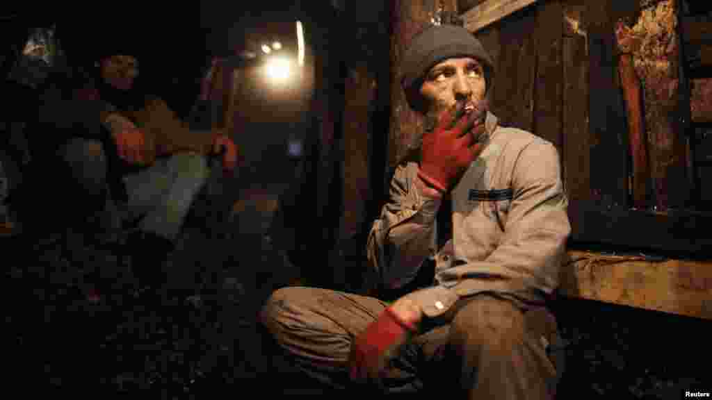 An illegal miner smokes a cigarrette during a break from digging in a coal mine in the village of Stranjani, near Zenica. There are about 20 illegal mines in the area, where Bosnians dig for coal with their bare hands and use makeshift tools, such as bathtubs, to transport the coal. One bag of their coal is sold for 3 euros ($4), which is popular with the locals as it is cheaper than the coal sold at the city mine. (Reuters/Dado Ruvic)