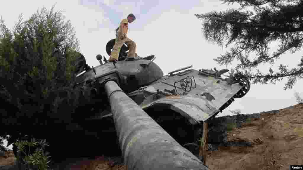 A boy walks on a damaged Syrian Army tank near Idlib on October 2. (REUTERS/Abdalghne Karoof)