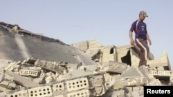 An Iraqi man inspects the site of a bomb attack at one of the homes of the police officers in Fallujah.