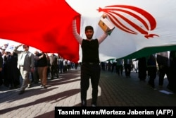 A pro-government demonstrator stands under an Iranian flag during a march in Iran's southwestern city of Ahvaz on January 3.