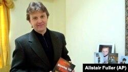 Aleksandr Litvinenko pozează cu cartea sa, Blowing Up Russia: Terror From Within, la casa sa din Londra în mai 2002.