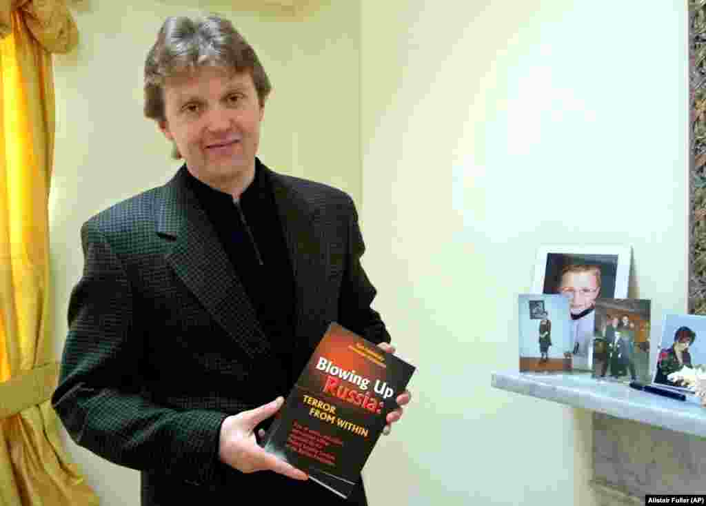 Litvinenko poses with his book, Blowing Up Russia: Terror From Within, at his home in London in May 2002. In the book, he accused the Russian secret services of staging the Russian apartment bombings in 1999 and other acts of terrorism in an effort to bring Vladimir Putin to power. Litvinenko fled Russia in 1999 after revealing an alleged plan by the FSB to kill tycoon Boris Berezovsky.