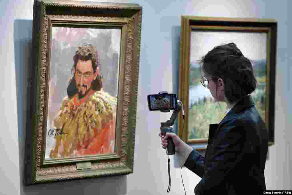 A woman livestreams an exhibition of works by Russian realist painter Ilya Repin in a Yekaterinburg museum on May 16.