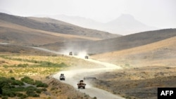 Afghan National Army (ANA) soldiers patrol the Shah Wali Kot district of Kandahar Province on May 23.