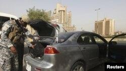 شرطي عراقي يتفحص سيارة في بغداد