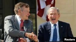 Үлкен Джордж Буш (сол жақта) пен кіші Джордж Буш (оң жақта) қол алысып отыр. Техас, 23 сәуір 2013 жыл.