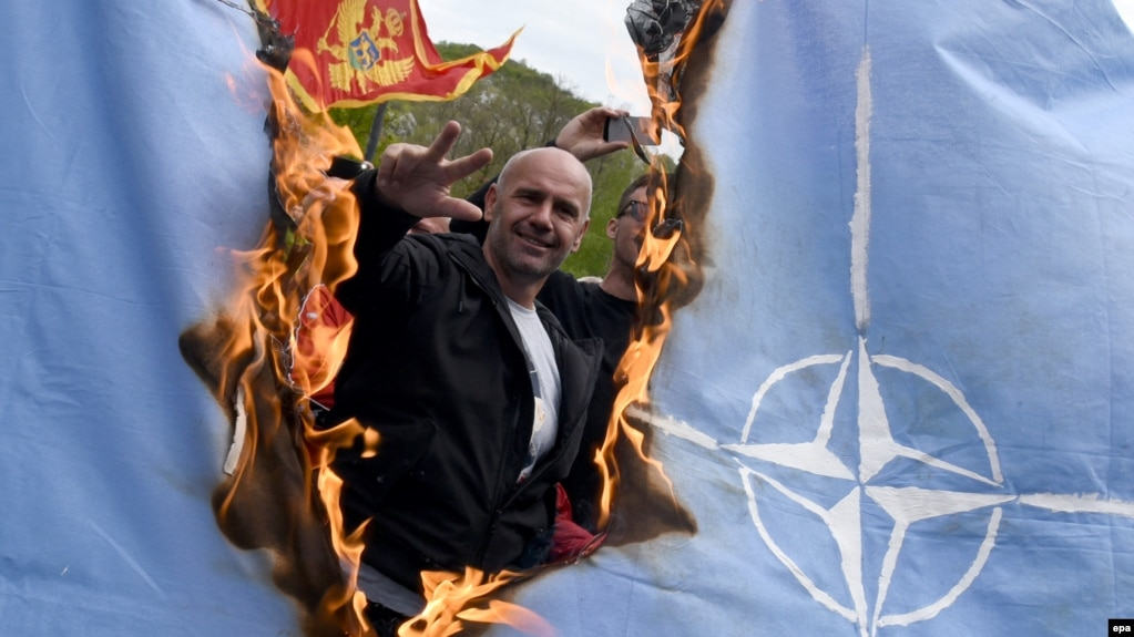Protesters burn a NATO flag while Montenegro's parliament discusses the ratification of a NATO membership agreement in Cetinje in April.