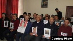 Казахи из Китая на пресс-конференции в Алматы с фотографиями своих родственников, которые, по их словам, помещены под стражу в «лагеря политического перевоспитания» в Синьцзяне. 20 декабря 2018 года.
