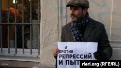 Ресейлік журналист азаптау мен саяси қуғын-сүргінге қарсы наразылық акциясында тұр. Мәскеу, 27 қазан 2012 ж.