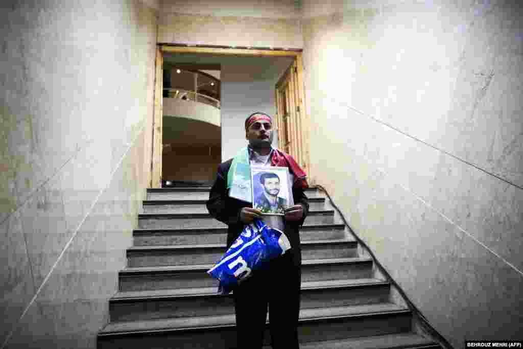 Rassoul Allahyari holds a portrait of Iranian President Mahmud Ahmadinejad as he arrives to register his candidacy for the upcoming presidential election at the Interior Ministry in Tehran. (AFP/Andrey Smirnov)