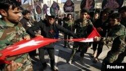 Архивска фотографија- Шиитски демонстрант кине турско знаме во знак на протест за зголеменото воено присуство во Басра, Ирач, 9 октомври