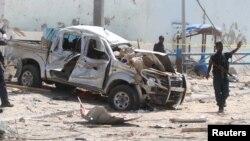 Поліцейський біля уламків автомобіля, зруйнованого під час теракту в Могадішо, 26 липня 2016 року