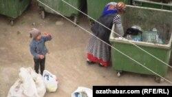 Женщина с ребёнком копается в мусорном контейнере в Ашхабаде (иллюстративное фото)