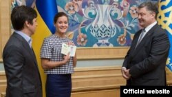 Maria Gaidar (center) holds aloft her newly issued Ukrainian passport, which was presented to her by President Petro Poroshenko (right). Journalist Vladimir Fedorin (left) was also granted Ukrainian citizensjip.