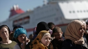 Greece--Refugee and migrant women line up as they wait to receive food distributed by Greek Red Cross at the port of Piraeus, near Athens, March 2, 2016.