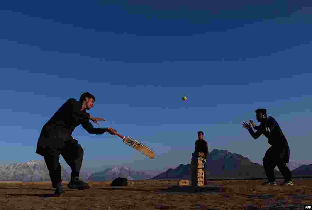 Afghan youths play cricket in a field on the outskirts of Kabul. (AFP/Wakil Kohsar)