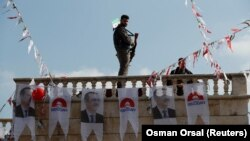 Një luftëtar i armatosur sirian, mbështetës i Turqisë, që qëndron mbi një ndërtesë në fshatin Sawran të Sirisë.