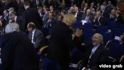 Германия «Жасылдар» партиясының басшысы Клаудия Рот (сол жақта) пен Иран елшісі Реза Шейх Аттардың амандасуы. Мюнхен, 2013 жылдың ақпаны.