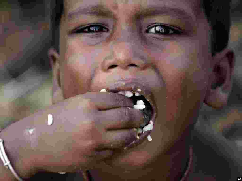 A child eats a meal distributed at a roadside relief camp for flood victims near Jajpur, India. (AP photo/Bikas Das)