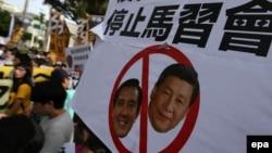 Протестующие в Тайбэе, столице Тайваня, с плакатом, где изображен бывший президент Тайваня Ма Инцзю и лидер Китая Си Цзиньпин. 4 ноября 2015 года.