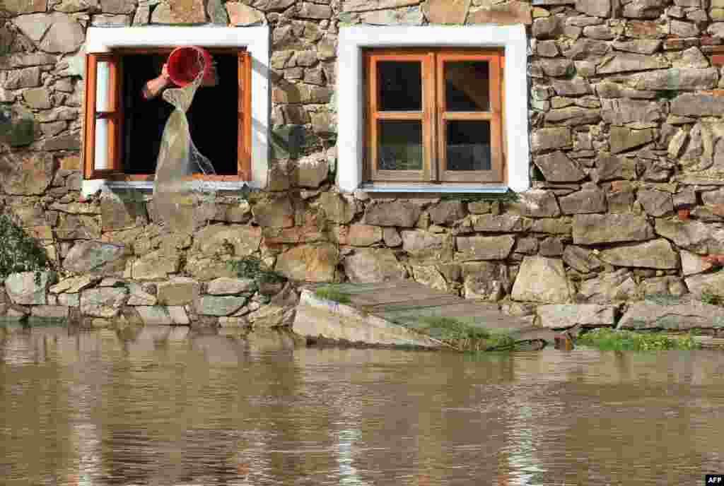 Человек ведрами вычерпывает воду из дома близ реки Бланице в деревне Путим в Чехии. В ходе проливных дождей затоплены некоторые города и деревни в Чехии, Австрии и Германии, есть жертвы.