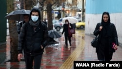 An Iranian man wears protective mask to prevent contracting coronavirus, as he walks in the street in Tehran, February 25, 2020