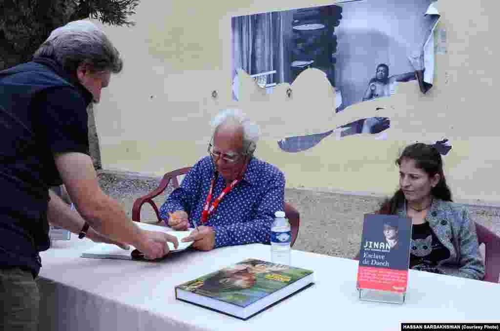 جنان بادل (راست) دختر ایزدیِ اسیرِ داعش و نویسندهکتاب «برده داعش»و پاسکال مائیتر، عکاس کتاب «آفریقای شگفتانگیز»، در حال امضای کتابهاشان.