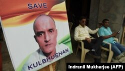 Residents sit next to a placard with a picture of Kulbhushan Sudhir Jadhav, an Indian national convicted of spying in Pakistan, in the neighborhood where he grew up, in Mumbai on July 17.