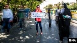 """Ирандык кыз """"Бизди санкция менен коркутпа"""" деген жазуусу бар плакатты кармап турат. Тегеран. 2015-жыл"""