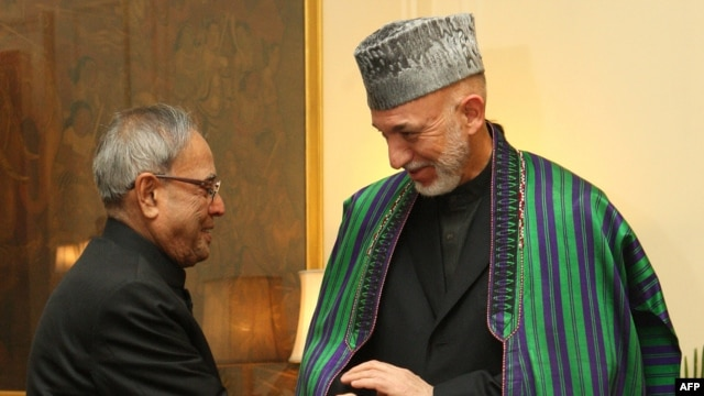 Indian President Pranab Mukherjee (left) greets his Afghan counterpart, Hamid Karzai, at the presidential palace in New Delhi.