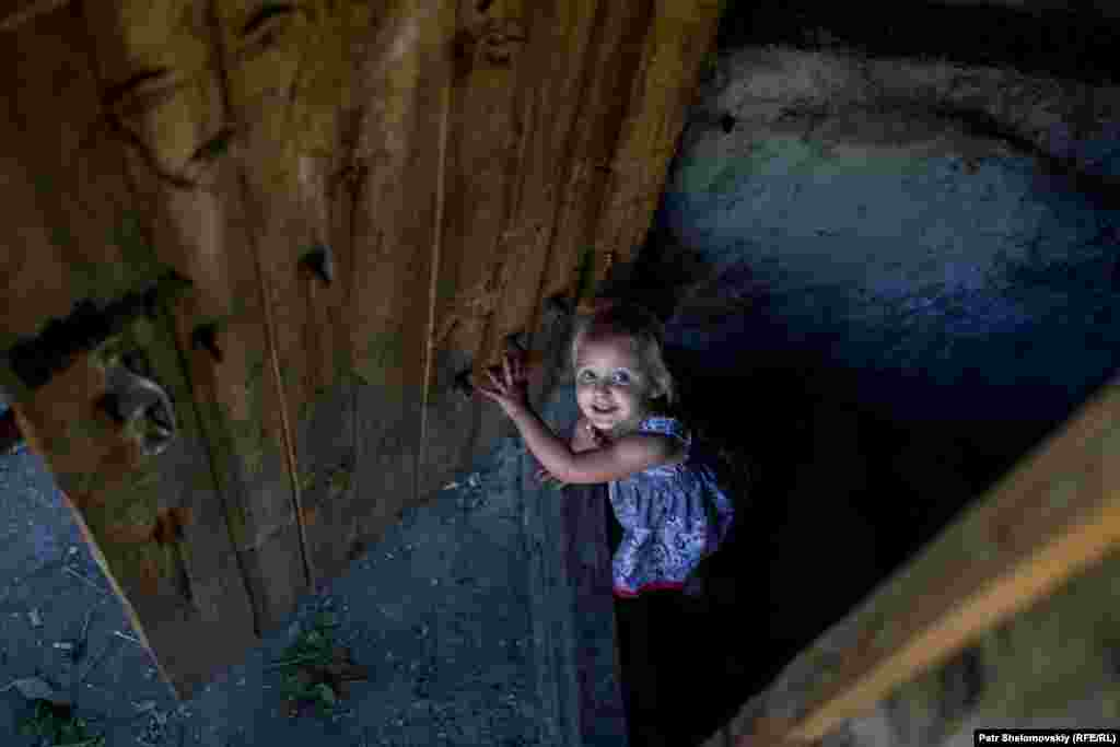 A girl leaves the bomb shelter in the Petrovskiy district. Some residents have lived in the basement dwelling for nearly a year.
