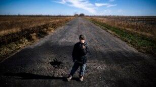 Хлопчик показує шматок шрапнелі після мінометного обстрілу українських позицій біля села Набережне