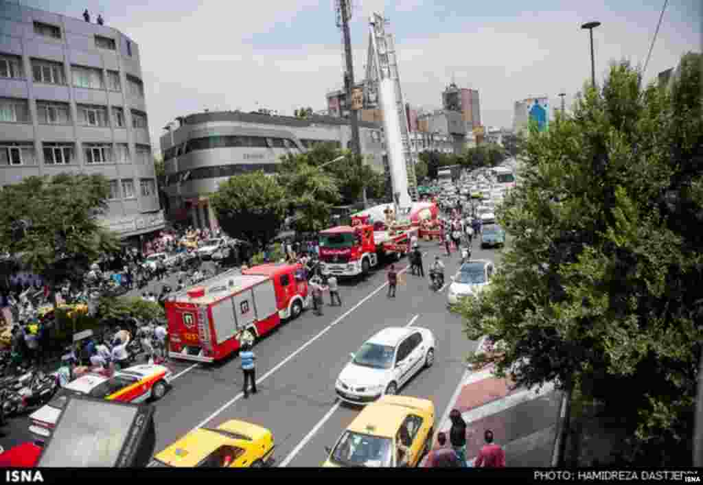 Crowds gather in Tehran's Haft-e Tir Square as emergency workers persuade the man to return to safety.