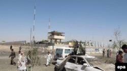 Afghan security officials inspect the site of a bomb attack in Helmand in June.