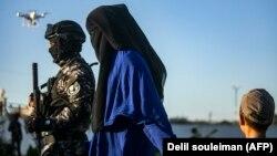 Повстанец в Сирии сопровождает женщину и ребенка, предположительно являющихся родственниками боевика группировки «Исламское государство».