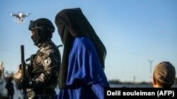 Сирияда экстремистік топтан азат етілген аймақтағы әскериге ілесіп келе жатқан әйел мен бала. Көрнекі сурет.