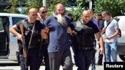 Косово полицейлері Сириядағы соғысқа қатысқан деген күдіктіні сотқа әкеле жатыр. Приштина, 12 тамыз 2014 жыл.