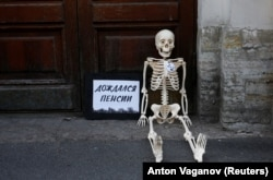 """Waited for pension"": A model skeleton lies on the ground during a protest against the government's plan to raise the pension age in St. Petersburg on July 19."