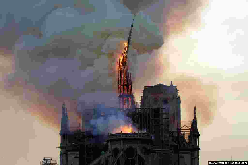 The steeple of the landmark Notre Dame Cathedral collapses as the cathedral is engulfed in flames in central Paris on April 15. (AFP/Geoffroy Van Der Hasselt)