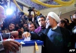 Президенттікке кандидат Хасан Рохани (оң жақта) сайлауда дауыс беріп тұр. Тегеран, 14 маусым 2013 жыл.